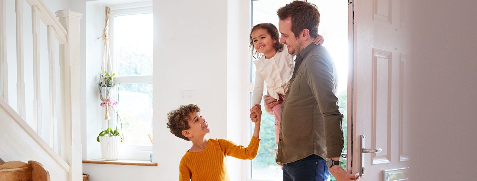 Dad, Son, and Daughter Walking Through Sunny Front Door